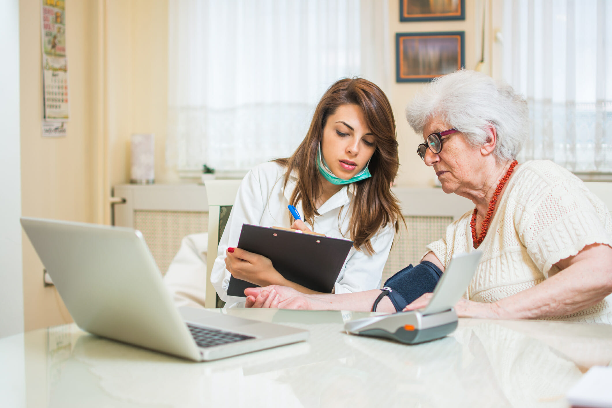 A nurse shows the senior citizen the data transmission of the blood pressure values to the doctor for remote treatment